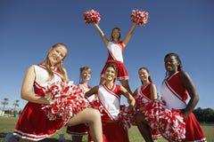 Glückliche Cheerleadern, die Pompoms auf Feld halten Stockbild