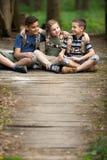 Glückliche childs im grünen spielenden Wald, Konzept von Kindern macht a Urlaub stockfotografie