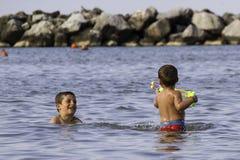 Glückliche childs spielen in Meer mit watergun, Ferien in Italien Lizenzfreie Stockfotos