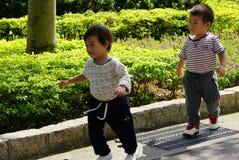 2 glückliche chinesische asiatische Kinder, die im Garten Daan Park Taipei Taiwan spielen stockbilder