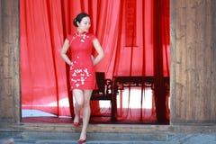 Glückliche chinesische Braut im roten cheongsam am traditionellen Hochzeitstag Stockfotografie