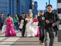 Glückliche chinesische Hochzeitspaare und -gäste gehen entlang das Embarcadero Stockbild