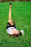 Glückliche Dame auf dem Gras, das Fahrwerkbein (2) ausdehnt Lizenzfreie Stockbilder