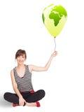 Glückliche Dame, die einen grünen Kugelballon anhält Lizenzfreie Stockbilder
