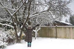 Glückliche Dame, die mit Schnee im Winter spielt Lizenzfreie Stockfotografie