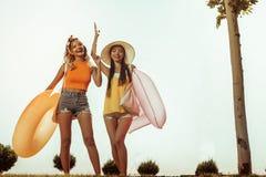Glückliche Damen, die Spaß beim Gehen zum Strand haben lizenzfreies stockbild