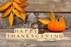 Glückliche Danksagungsholzklötze gegen rustikales Holz mit Herbstlaub Stockfotos
