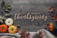 Glückliche Danksagungstypographie mit Kürbisen und Blättern über dunklem hölzernem Hintergrund lizenzfreie stockfotografie