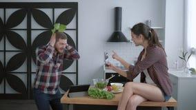 Glückliche Diät, nettes Mädchen werden am Handy des lustigen Kerls, beim Kochen der gesunden Nahrung für das Mittagessen und mach stock video footage