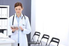 Glückliche Doktorfrau bei der Arbeit Porträt des weiblichen Arztes, der Tablet-Computer bei der Stellung des nahen Aufnahmeschrei stockfotografie