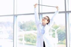 Glückliche Doktorfrau, die im Krankenhausbüro an einem sonnigen Tag lächelt Stockfotos