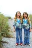 Glückliche Doppelschwestern auf der Strandvertikale Stockbild