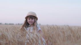 Glückliche Dorfkindheit, wenig nettes Mädchen mit dem Strohhut, der Spaß hat und Drehbeschleunigungen in geernteten Kornweizenspi stock video footage