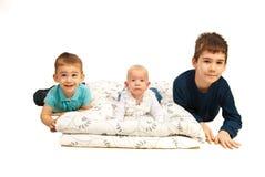 Glückliche drei Kinder, die sich in einer Zeile hinlegen Lizenzfreies Stockbild