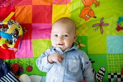 Glückliche drei Monate alte Baby, zu Hause spielend auf einem bunten a Lizenzfreie Stockbilder