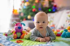 Glückliche drei Monate alte Baby, zu Hause spielend auf einem bunten a Stockbild