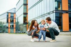 Glückliche dreiköpfige Familie des Porträts Junge Eltern spielen mit ihrer kleinen Tochter beim Gehen durch die Straßen der Stadt lizenzfreies stockfoto