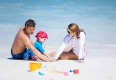 Glückliche dreiköpfige Familie, die auf dem Strand, ihre Hände auf einander setzend spielt stockfotos