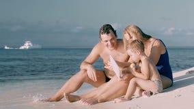Glückliche dreiköpfige Familie, die durch das Meer und die Anwendung sitzt stock footage