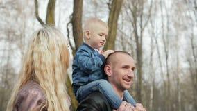 Glückliche dreiköpfige Familie, die im Frühjahr Park geht stock video footage