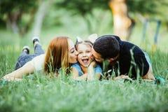 Glückliche dreiköpfige Familie, die im Gras im Sommerpark liegt lizenzfreie stockfotos
