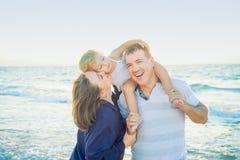 Glückliche dreiköpfige Familie - schwangere Mutter, Vater und Tochter, die Spaß gehend auf den Strand umfasst, laughhing und hat  stockbild