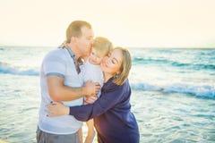 Glückliche dreiköpfige Familie - schwangere Mutter, Vater und Tochter, die Spaß gehend auf den Strand umfasst, laughhing und hat  stockfoto