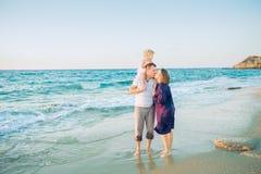 Glückliche dreiköpfige Familie - schwangere Mutter, Vater und Tochter, die Spaß gehend auf den Strand umfasst, laughhing und hat  stockbilder