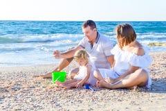 Glückliche dreiköpfige Familie - schwangere Mutter, Vater und Tochter, die Spaß, spielend mit Sand und Oberteilen auf dem Strand  stockbilder