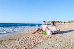 Glückliche dreiköpfige Familie - schwangere Mutter, Vater und Tochter, die Spaß, spielend mit Sand und Oberteilen auf dem Strand  stockfotografie