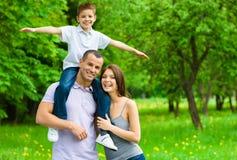 Glückliche dreiköpfige Familie. Vater hält Sohn auf Schultern Stockbilder