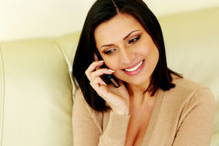 Glückliche durchdachte Frau, die am Telefon spricht stockfotografie