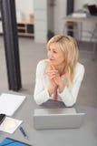 Glückliche durchdachte Geschäftsfrau Sitting an ihrem Schreibtisch Stockbild