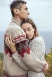 Glückliche durchdachte Paare, die auf einer Klippe nahe dem Meer umarmt eac stehen lizenzfreies stockbild