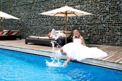 Glückliche eben wedding Paare nähern sich Pool Lizenzfreie Stockfotografie