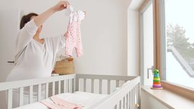 Glückliche Einstellungsbabykleidung der schwangeren Frau zu Hause stock video footage