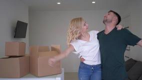 Glückliche Einzugsfeier, Hauseigentümerspaßtanzen der netten jungen Paare neues und Vergnügen zur neuen Wohnung mit Kästen n stock footage