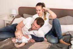 Glückliche Eltern, die mit ihrem neugeborenen Kind spielen Stockbild
