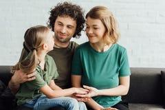 glückliche Eltern, die nette kleine Tochter beim Sitzen auf Couch betrachten lizenzfreies stockfoto