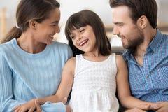 Gl?ckliche Eltern entspannen sich auf Couch mit weniger Tochter lizenzfreies stockfoto