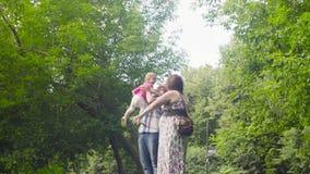Glückliche Eltern mit Baby in einem Park stock footage