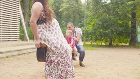 Glückliche Eltern mit dem Baby, das auf einem Schwingen schwingt stock footage