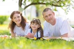 Glückliche Eltern mit dem Baby im Park stockfotografie