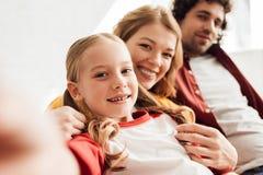 glückliche Eltern mit dem netten wenig Tochterlächeln stockfoto