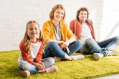 glückliche Eltern mit der entzückenden kleinen Tochter, die an der Kamera beim zusammen sitzen lächelt stockfotografie
