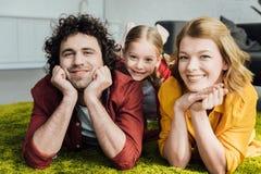 glückliche Eltern mit der entzückenden kleinen zusammen liegenden und lächelnden Tochter lizenzfreie stockfotografie