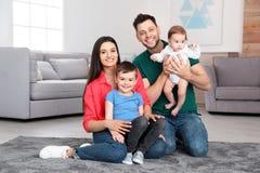 Glückliche Eltern und ihre nette Kinder, die zu Hause auf Boden sitzen stockfotografie