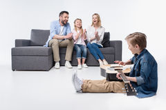 Glückliche Eltern und nette kleine Schwester, die zum Jungen spielt Gitarre applaudiert stockbild
