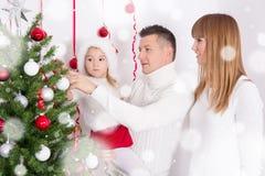 Glückliche Eltern und Tochter, die Weihnachtsbaum verziert Stockfoto