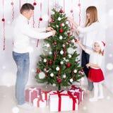 Glückliche Eltern und Tochter, die zu Hause Weihnachtsbaum verziert Stockbild